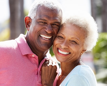 Happy smiling, mature couple who had their smiles restore with crowns and bridges in our Wichita KS dentist office.