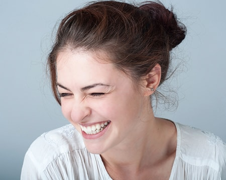 A young woman laughing with healthy gums thanks to our family dentistry in Wichita, KS