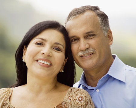 Older couple smiling thanks to receiving dental implants from Wichita cosmetic dentists, Dr. Volker and Dr. Meng.