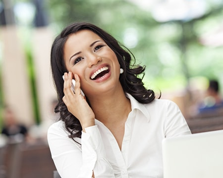 A professionally dressed woman laughing on the phone with a beautiful smile thanks to cosmetic dentistry in Wichita KS