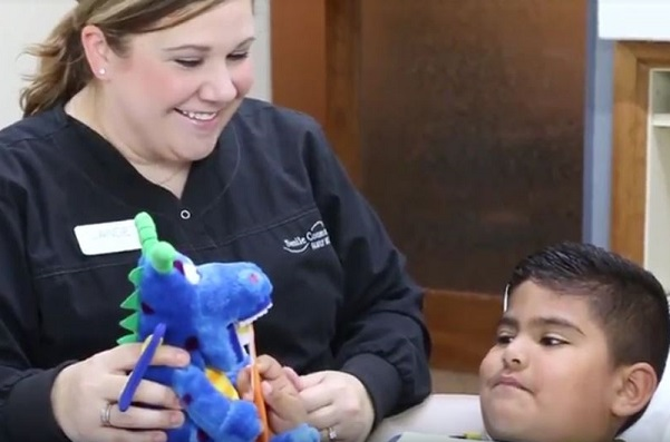 Hygienist showing little boy how to brush his teeth by using a dinosaur visual aid.