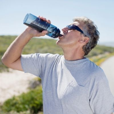 A man chugging water following dietary counseling for preventive dentistry